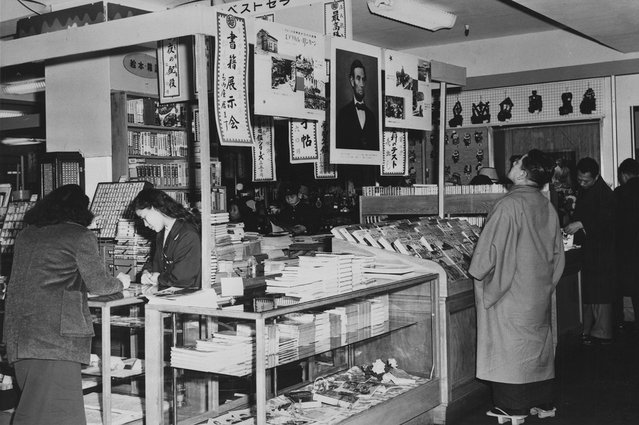 Interior dari sebuah department store di Tokyo pada 1959, dimana seorang pria Jepang mengenakan Geta, sandal kayu tradisional, sedang melihat foto Abraham Lincoln digantung bersama dua poster lain tentang kehidupan Lincoln. (Photo by Library of Congress via The Atlantic)