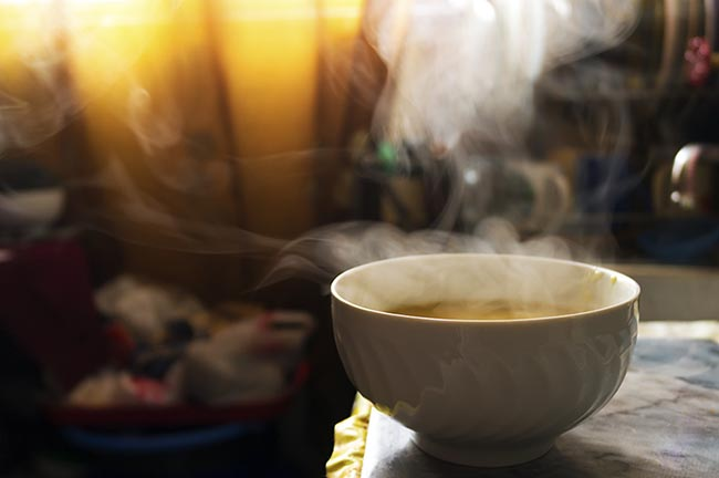 Steaming hot soup in a bowl in the kitchen under warm sunlight