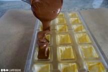 Die Pralinenform randvoll mit temperierter Schokolade füllen.