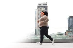 Beautiful overweight woman running outdoors.