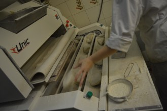 Margot then throws the doughballs into the balancelle (stretching machine), where the bread is stretched out (tournage). It's pretty strenuous doing it manually. 'Traditions' come out shorter than 'baguettes' (55-65 cm) but weigh the same before being cooked (between 250 and 300g)