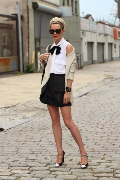 Elle porte une jupe classique avec un chemisier blanc, des chaussures habillées et un gilet long beige.