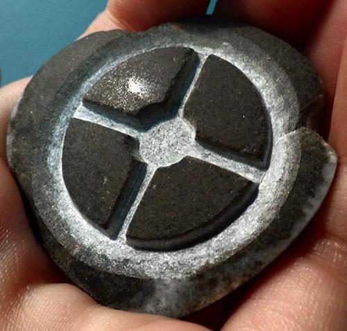 Logo du jeu vidéo Team Fortress 2 en relief sur un galet poli