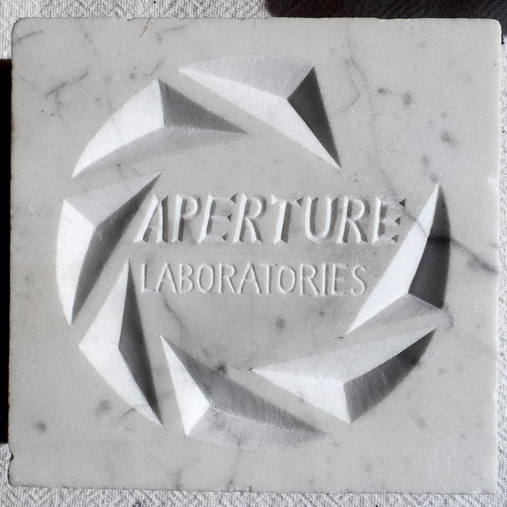 Logo de l'entreprise fictive Aperture Science (Portal) gravée en marbre blanc. We do it because we can.