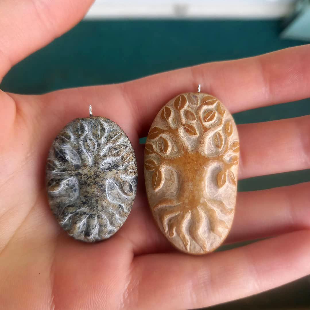 2 pendentifs sculptés à partir de petits galets représentant chacun un arbre.