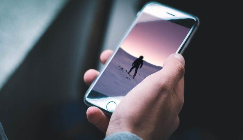 Black iPhone in male Hand Mockup