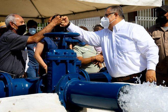 pozo agua potable dos funcionarios hombres chocan puños