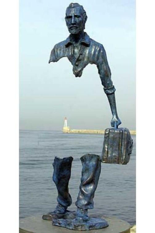 uomo migrante con valigia sul molo