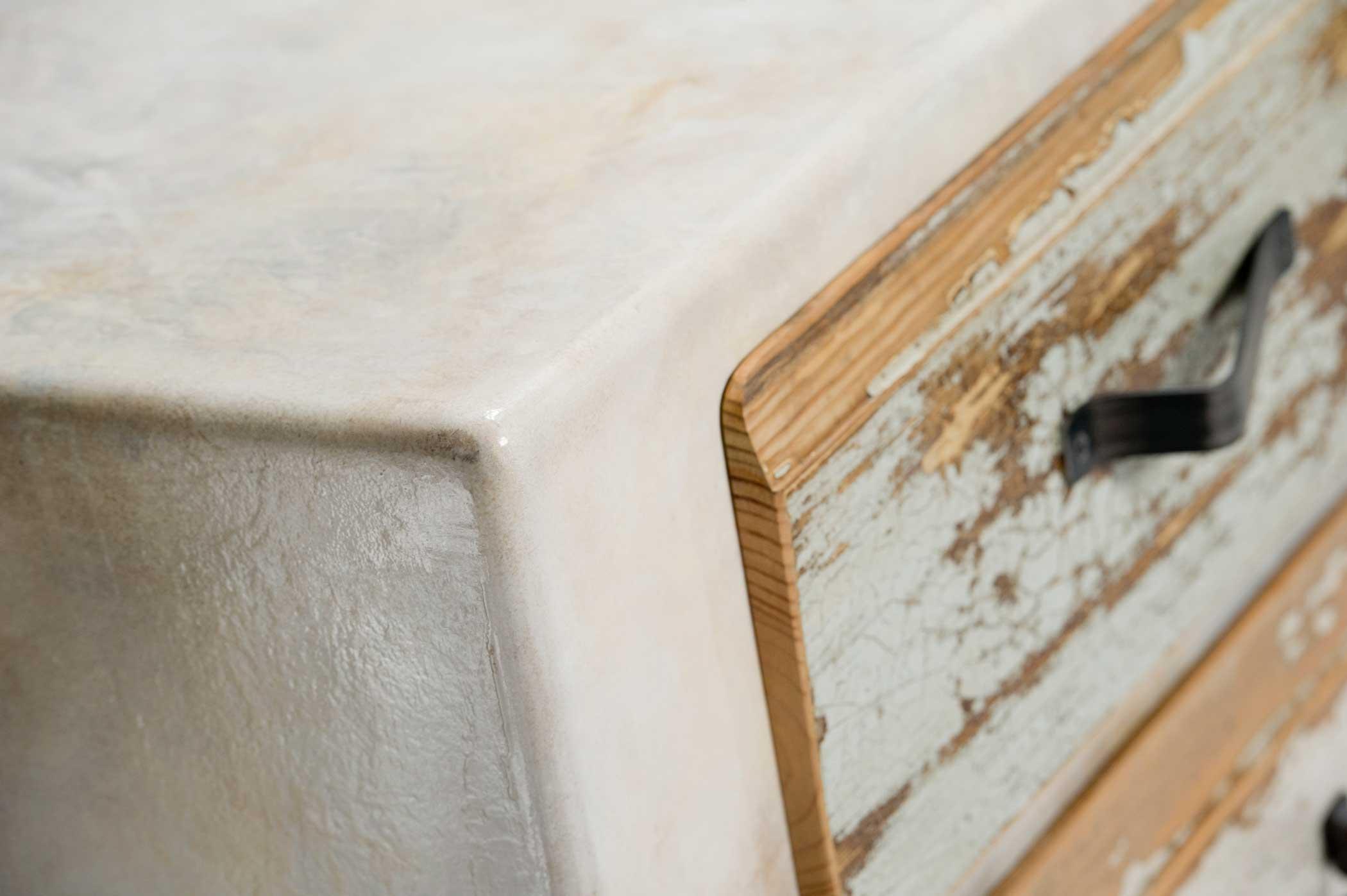 Cassettiera con maniglia in ferro ossidato, legno dei cassetti scrostato.