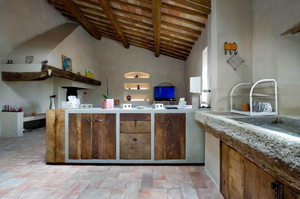 Cucina in muratura con ante in castagno vintage antico bruciato. Legno riusato