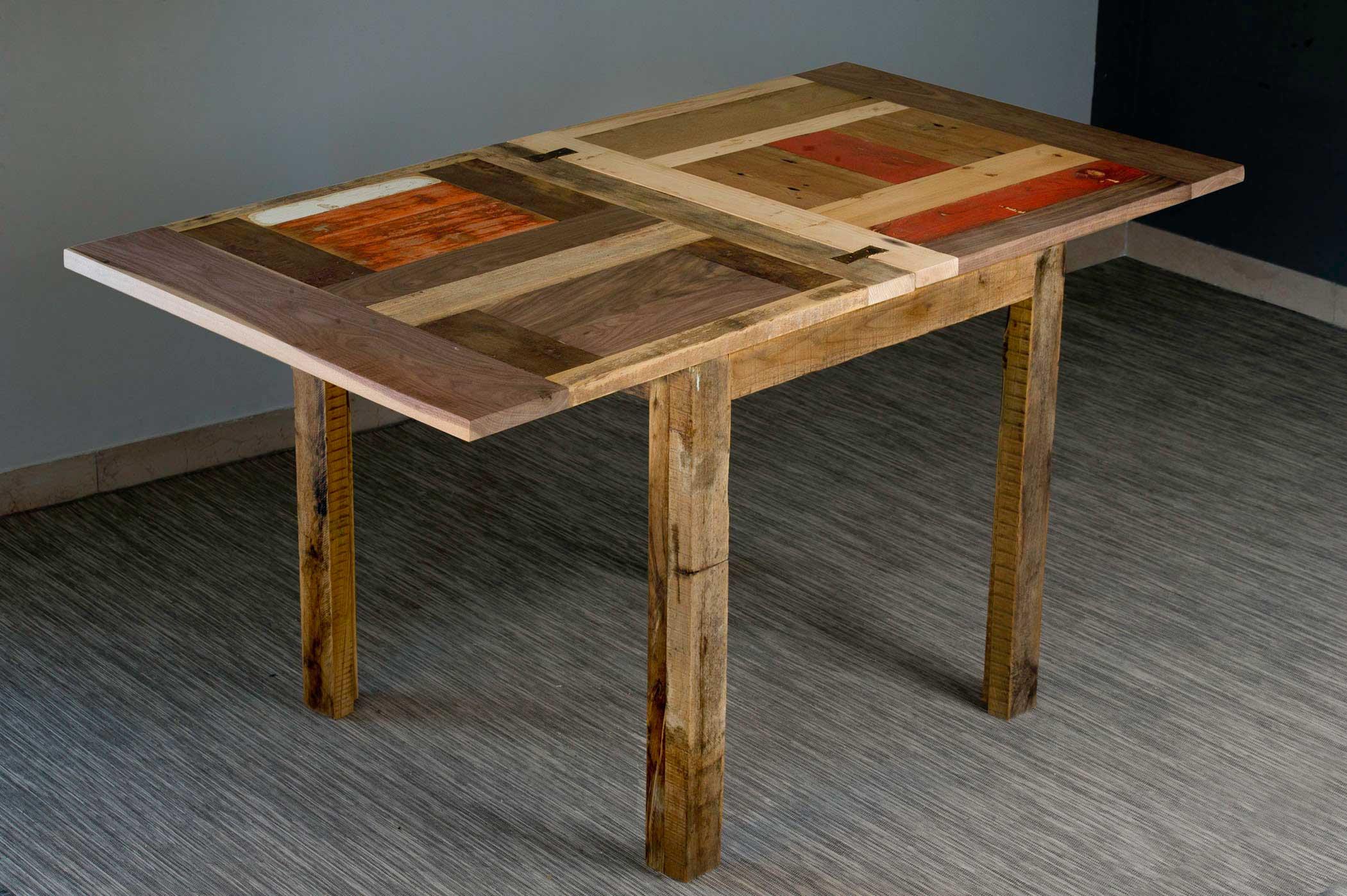 Tavolo allungabile interamente in legno di rovere massello con inserti di legno di recupero colorato. Piano del tavolo doppio e ribaltabile