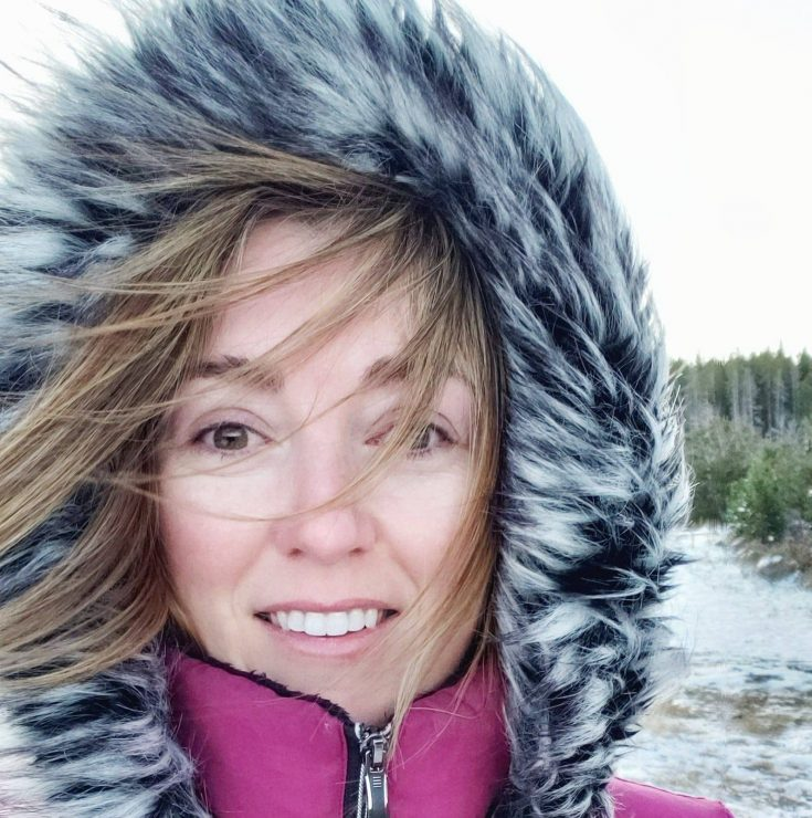 image of a girl in a pink jacket with fury hood smiling
