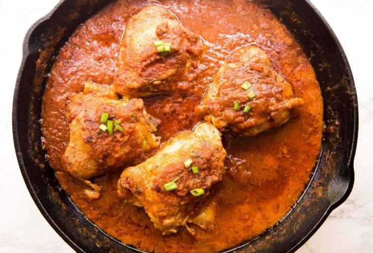 coconut milk chicken thighs in a pan surrounded and covered in a red sauce