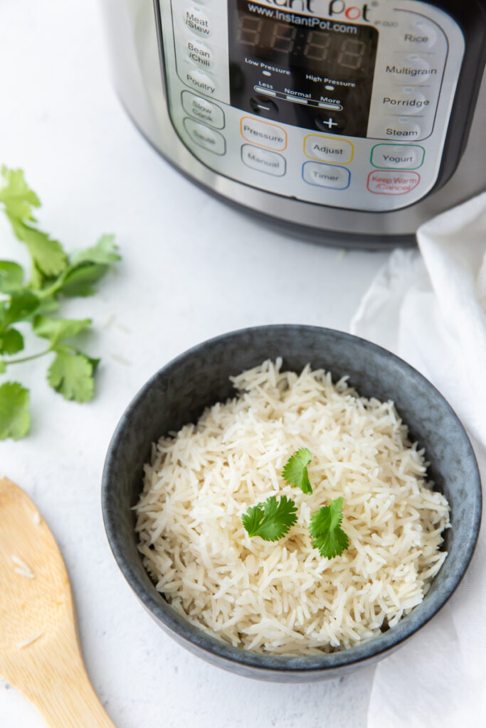 over head shot of a blue bowl filled with basmati rice topped with cilantro