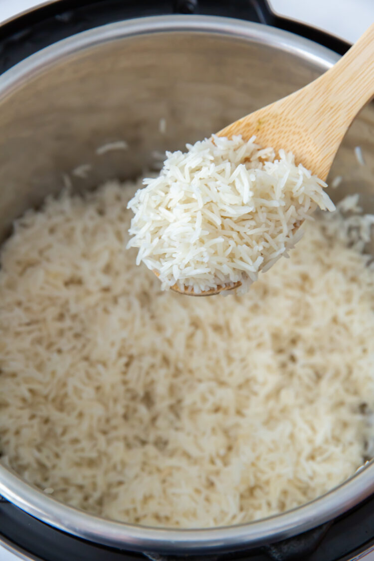 a wooden spoon with a spoonful of basmati rice