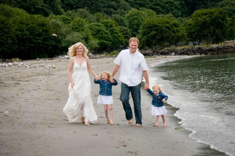 Family Photo Of Parents Holding Hands With Children While Walking Down Beach By Seattle Photographer Lara Grauer Photography