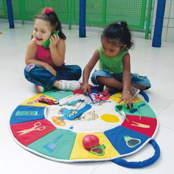 Duas meninas de aproximadamente 4 anos, sentadas lado a lado, em frente ao painel circular do Ciranda das Cores. A que está à esquerda, tem nas mãos, um celular de plástico e a que está à direita, segura alguns dos objetos que compõem o brinquedo.
