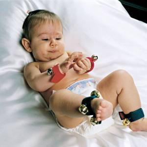 Bebê deitado sob um tapete branco, com Guizos nos pés e nas mãos. Com a mão direita, toca a pulseira que está em seu pulso esquerdo.