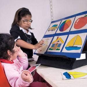 Duas meninas de aproximadamente 6 anos, em frente ao painel do Sexteto em Cores. Em primeiro plano, sentada, uma menina de cabelos escuros, na altura dos ombros e à sua frente, um cartão com a figura de uma maçã. À sua esquerda, em pé, uma menina de cabelos escuros, lisos, na altura dos ombros, de óculos, com a mão sobre o cartão com a figura de um rosto.