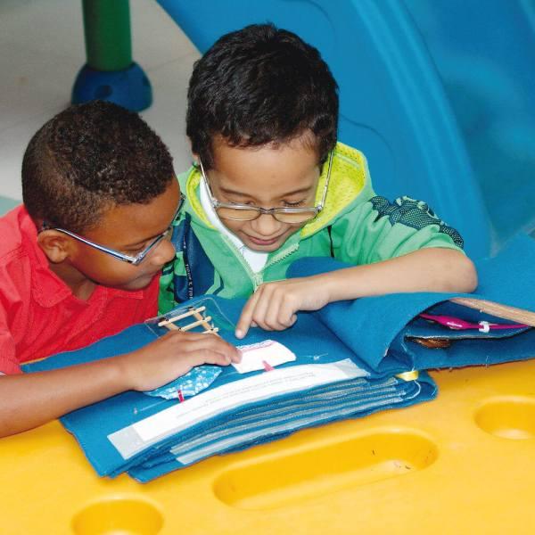 Sentados em frente à uma mesa amarela, dois meninos de aproximadamente 6 anos, cabelos escuros, curtos e óculos, tocam com as mãos, uma página do livro Ajudando a Mamãe.