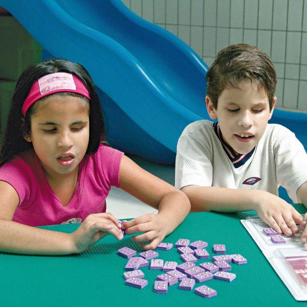 Uma menina e um menino de aproximadamente 7 anos, sentados lado a lado, em frente à uma mesa verde. Ambos têm nas mãos, algumas celas do Brailito.