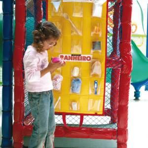 Menina de aproximadamente 6 anos, está em pé, em frente ao tapete amarelo do brinquedo Como Gente Grande. Na mão direita, segura um dos objetos que compõem o brinquedo.
