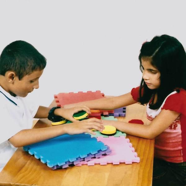 Menino e menina de aproximadamente 7 anos, sentados um em frente ao outro e à frente deles, uma mesa de madeira, onde está o Cubo Surpresa. Com as mãos, tocam os círculos e as peças de encaixe.