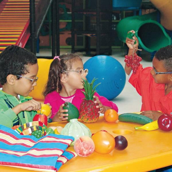 Dois meninos e uma menina de aproximadamente 5 anos, sentados em frente a uma mesa amarela, onde estão as frutas de plástico e a sacolinha do brinquedo Feirinha.