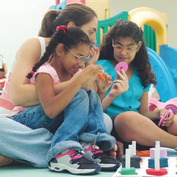 Duas meninas de aproximadamente 7 anos, cabelos escuros e cacheados, usam óculos. Estão sentadas e à sua frente, a prancheta do Formas e Números. Ambas têm nas mãos, figuras geométricas de encaixe. Atrás delas, a mediadora apresenta o círculo.