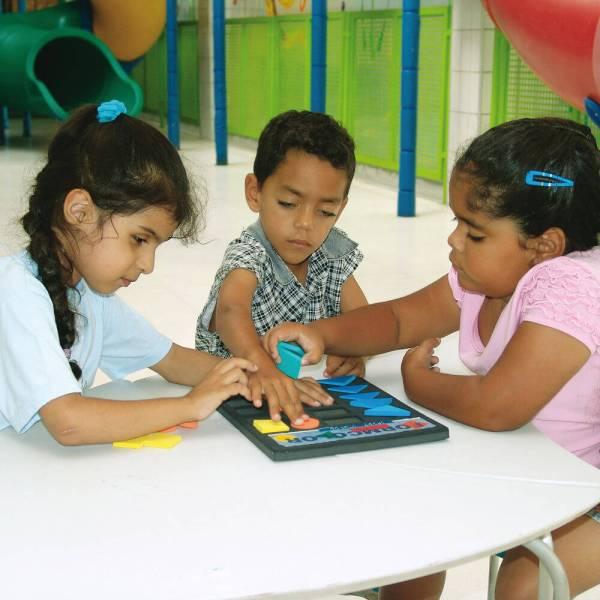 Duas meninas e um menino, de aproximadamente 3 anos, estão sentados, lado a lado, em frente à uma mesa branca. No centro da mesa, o brinquedo Form Color. Os três têm nas mãos, uma forma geométrica.