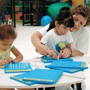 Duas meninas de aproximadamente 5 anos, sentadas. À sua frente, placas do Forme Formas. Ambas têm nas mãos, os pinos de encaixe.
