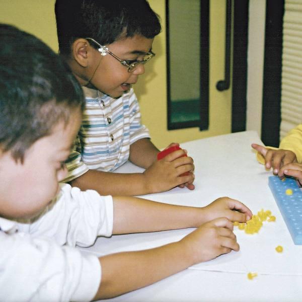 Dois meninos de aproximadamente 5 anos, sentados lado a lado, em frente à uma mesa branca, onde está o Brailindo. O que está à esquerda, toca pinos amarelos espalhados sobre a mesa e ao seu lado, um menino tem nas mãos uma caixinha vermelha.