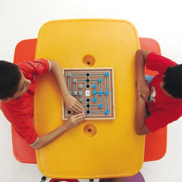 Dois meninos, sentados um em frente ao outro, em frente à uma mesa amarela, onde está o tabuleiro da Trilha. O que está à esquerda, toca uma peça, enquanto o outro, observa.