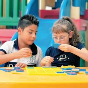 Um menino e uma menina de aproximadamente 6 anos, sentados em frente à uma mesa amarela, onde está o Jogo da Memória. Ela segura um quadrado azul com a mão esquerda, enquanto ele observa.