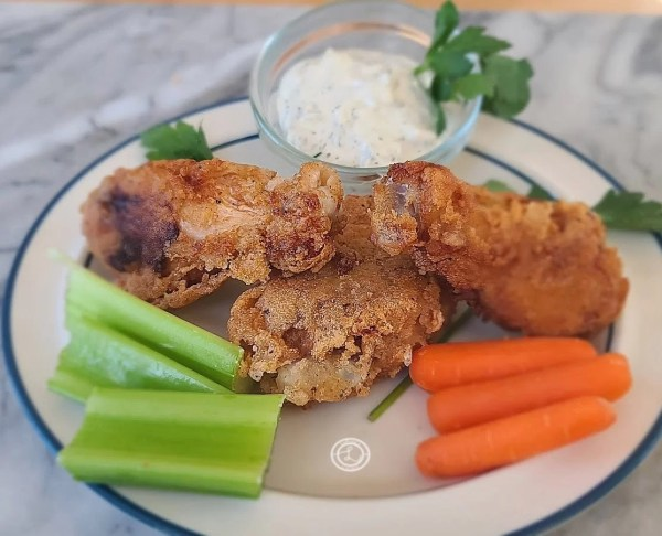 4 wings on a plate with celery, carrots, and ranch.
