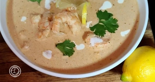 Oyster-Bar Shrimp Pan Roast in a bowl with a slice of lemon, cilantro, and splashes of cream to decorate