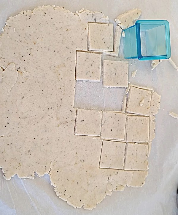 Cutting out crackers with a cookie cutter.