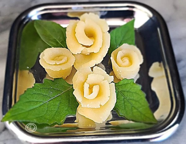 Homemade From Scratch Marzipan Roses on a silver tray with basil leaves.