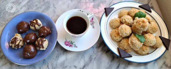 Cookies both dipped and undipped on plates. and a cup of coffee
