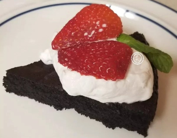 Flourless Chocolate Cake with whipped topping, slced strawberries and mint