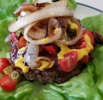 Cooked burger on lettuce, grape tomatoes, bread and butter pickles, BBQ sauce, mustard and caramelized onions
