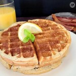 Sweet and Tart Lemon Waffles on a plate with orange juice and bacon in the background.