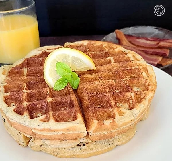 Gluten-Free Sweet-n-Tart Lemon Waffles with orange juice and bacon, a slice of lemon, and sprig of mint.
