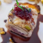 Chicken Roulade that has been cut into and on top of glaze