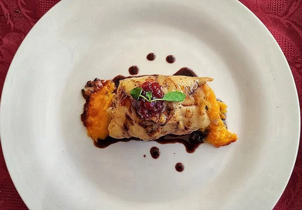 Smokey Pomegranate Chicken Roulade on a plate with drops of glaze on the plate