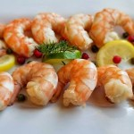 Cooked Lemon Dill Shrimp On a platter with lemon and lime slices with dill and lingonberries
