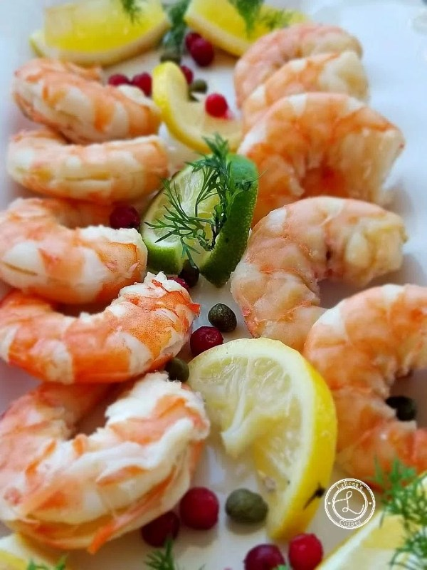 Scandinavian Dill Shrimp on a plate with lime and lemons