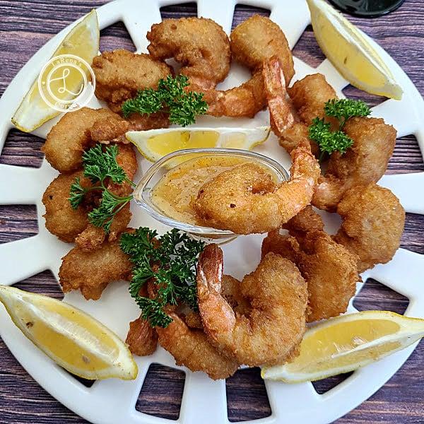 Gluten-Free Coconut Shrimp on an oval platter with lemon wedges