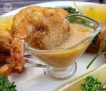Orange Horseradish Dipping Sauce with a piece of coconut shrimp