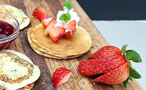 Swedish Pancakes with strawberries, whipped cream, lingonberry jam, and spring of mint.